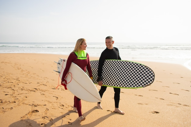 Surfistas felices alejándose de la playa y hablando