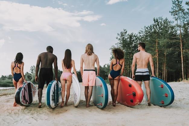 Los surfistas hacen cola. concepto de vista posterior.