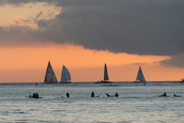 Surfistas en la playa con veleros en el fondo al atardecer, waikiki, honolulu, oahu, hawaii, ee.uu.