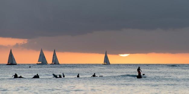 Surfistas con veleros en el fondo al atardecer, waikiki, honolulu, oahu, hawaii, estados unidos