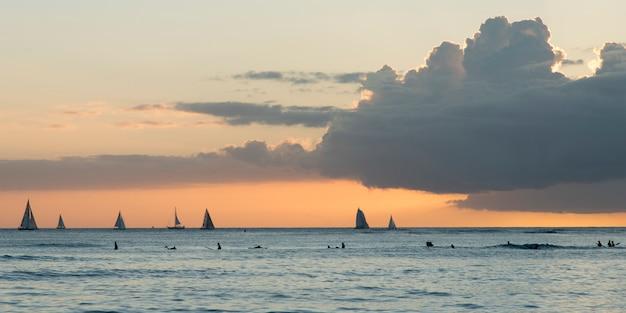 Surfistas y veleros en el océano al atardecer, waikiki, honolulu, oahu, hawaii, estados unidos
