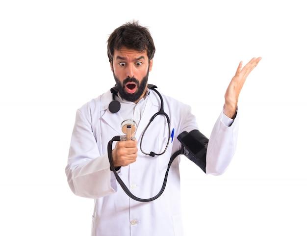 Surpreendido médico con monitor de presión arterial sobre fondo blanco