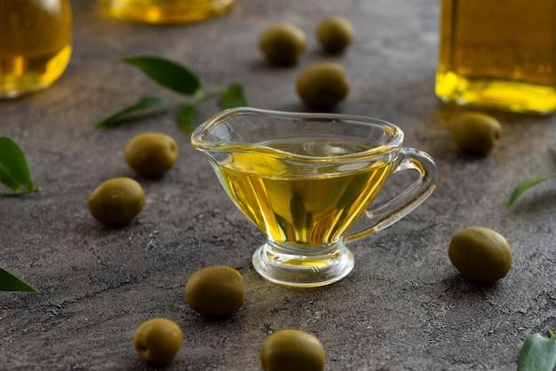 Surtido de aceite de oliva en vidrio y aceitunas verdes.