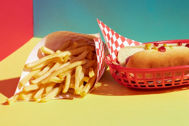 Surtido de ángulo alto con papas fritas y hot dog en la canasta