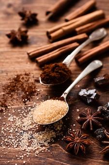 Surtido de canela natural, azúcar moreno de caña, café molido, ingredientes para hornear estrellas de anís en una rústica mesa marrón.