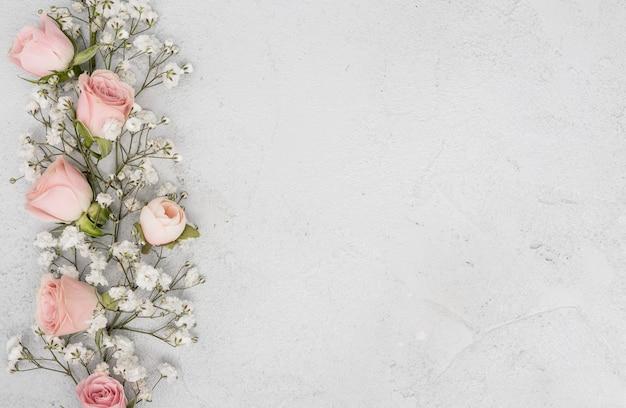 Surtido de capullos de rosas rosadas y flores blancas.