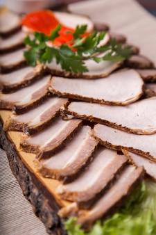 Surtido de carne ahumada. cerdo ahumado y ternera ahumada sobre tabla de madera. merienda fría