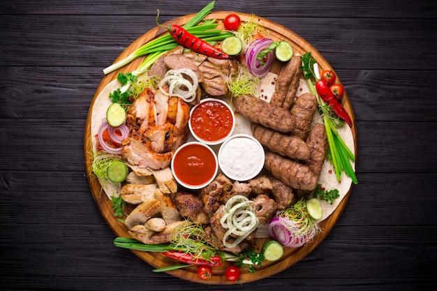 Surtido de carnes a la brasa y verduras en mesa rústica.