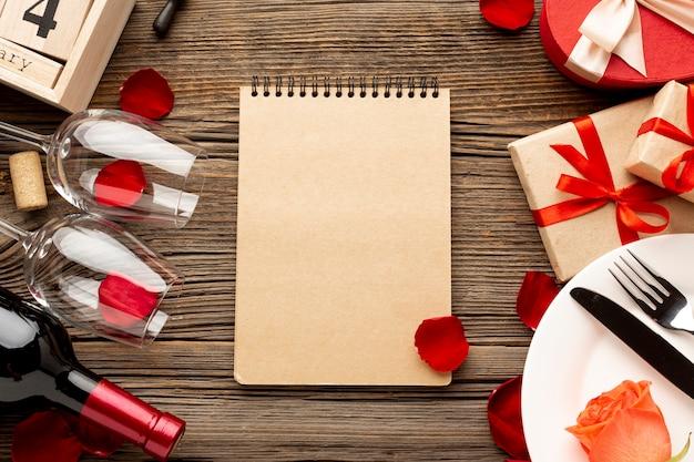 Surtido de cena del día de san valentín con bloc de notas vacío