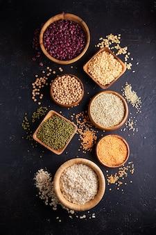 Surtido de cereales, legumbres, cereales, granos, lentejas, garbanzos, guisantes, frijoles, avena en cuencos de madera.