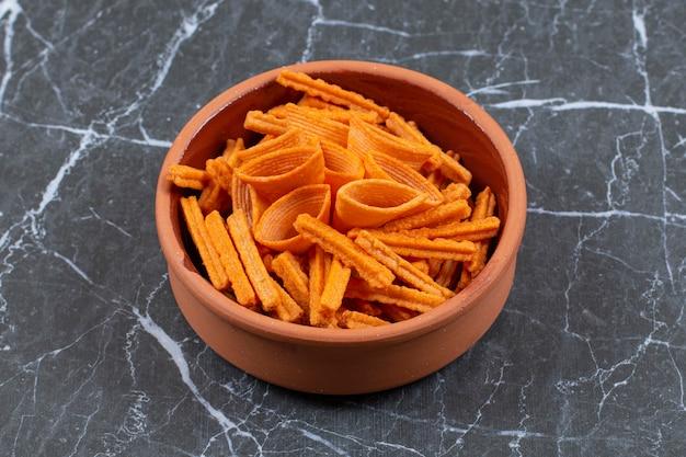 Surtido de chips con especias en cuenco de cerámica.