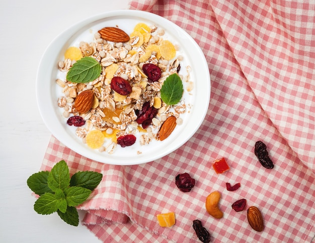 Surtido de coloridas frutas frescas con yogurt en tazón de cerámica.