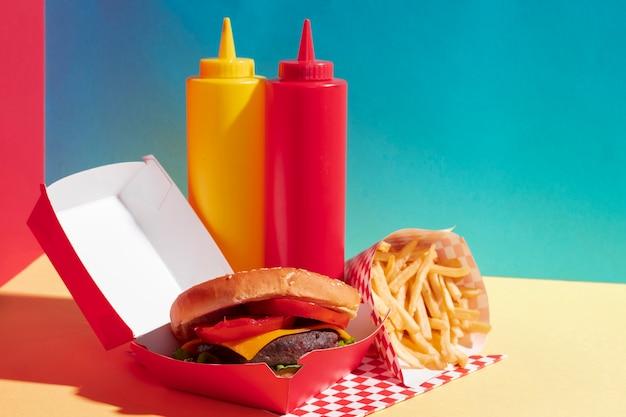 Surtido de comida con hamburguesas y botellas de salsa.