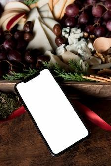 Surtido de comida navideña de alto ángulo con smartphone vacío