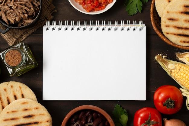 Surtido de comida de vista superior con cuaderno
