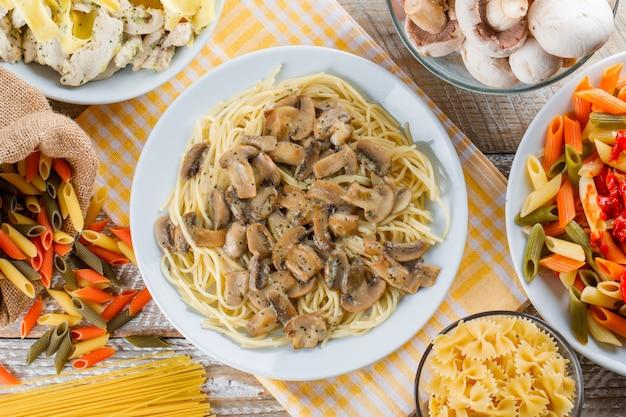 Surtido de comidas de pasta en platos con pasta cruda y champiñones.