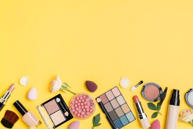 Surtido de cosméticos con espacio de copia sobre fondo amarillo.