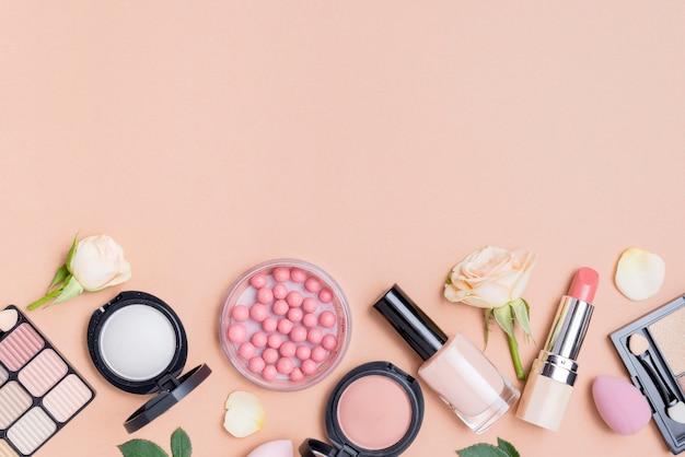 Surtido de cosméticos con espacio de copia sobre fondo beige