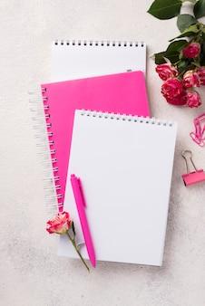 Surtido en cuadernos con bolígrafo y ramo de rosas.