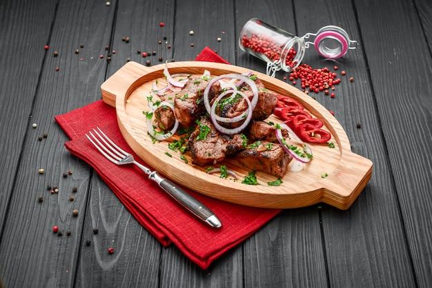 Surtido de deliciosas carnes a la parrilla con vegetales en un plato blanco mesa de picnic para la fiesta familiar de barbacoa