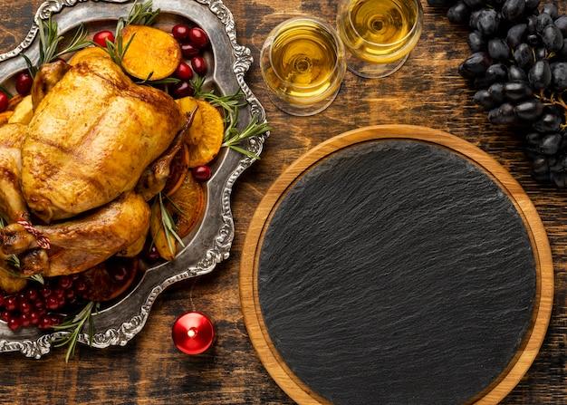 Surtido de deliciosos platos navideños con tablero de madera negro vacío