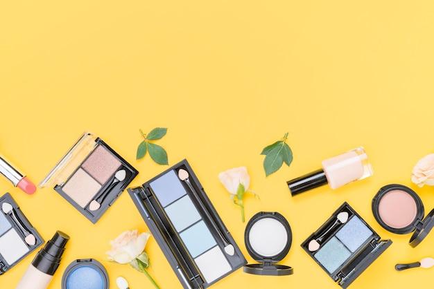 Surtido de diferentes cosméticos con espacio de copia sobre fondo amarillo.