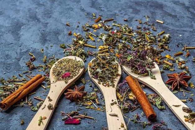 Surtido de diferentes tés secos en cucharas de madera con anís y canela en estilo rústico