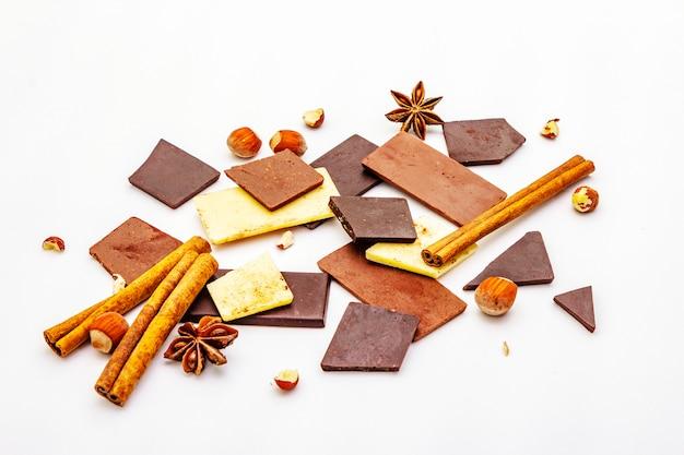 Surtido de diferentes tipos de chocolate, especias y avellanas sobre blanco.