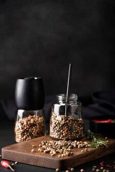 Surtido de diferentes tipos de pimienta de jamaica en un frasco de vidrio sobre una tabla de madera