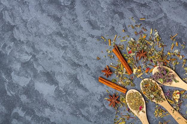 Surtido de diferentes tipos de té seco y jengibre, anís y canela en cucharas de madera en estilo rústico.