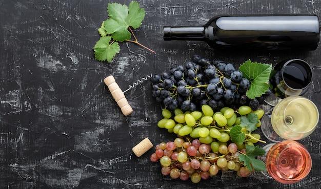 Surtido de diferentes tipos de vino y variedades de grado. degustación de vino tinto rosa blanco en vasos cerca de uvas blancas rosadas y negras, botella de vino tinto sobre fondo de hormigón oscuro.