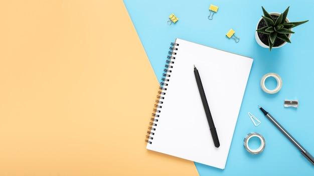 Surtido de elementos de escritorio con bloc de notas vacío con espacio de copia