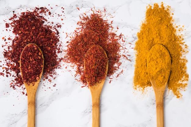 Surtido de especias coloridas en las cucharas de madera.