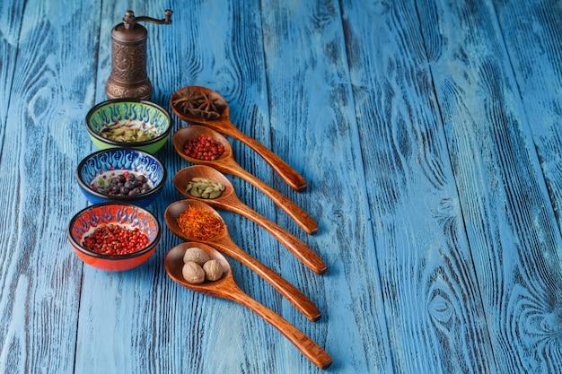 Surtido de especias en cucharas de madera en mesa de madera