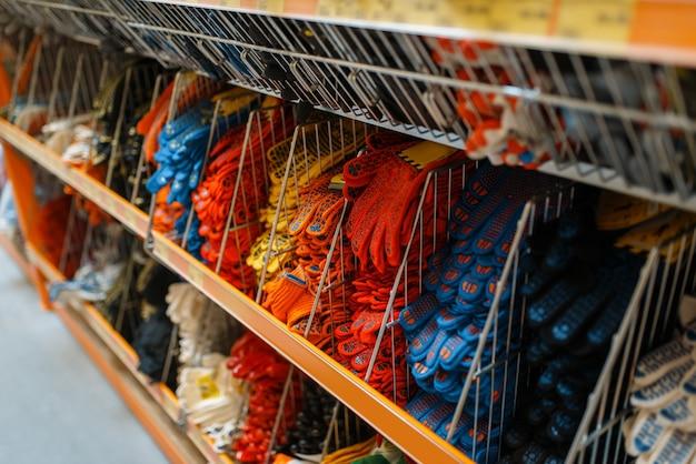 Surtido de ferretería, estante con guantes, nadie. elección de materiales y herramientas de construcción en la tienda de bricolaje, filas de productos en bastidores