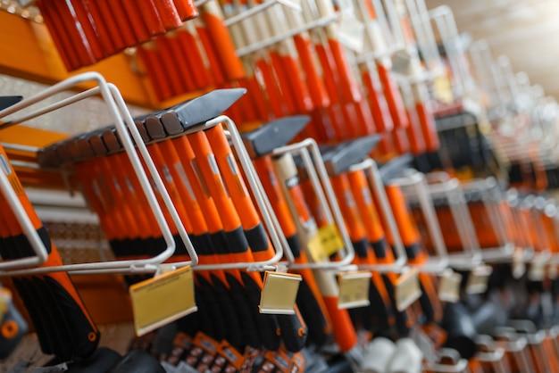 Surtido de ferretería, estante con martillos, nadie. elección de materiales y herramientas de construcción en la tienda de bricolaje, filas de productos en bastidores