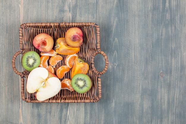 Surtido de frutas en una canasta de mimbre sobre la mesa de madera