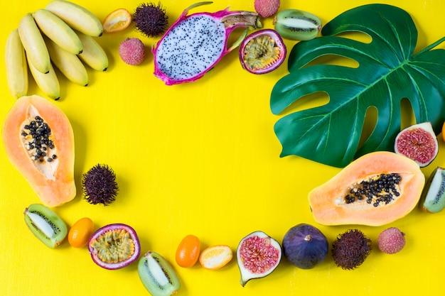 Surtido de frutas exóticas y hojas de monstera