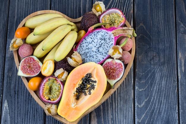 Surtido de frutas exóticas en un plato de madera en forma de corazón.