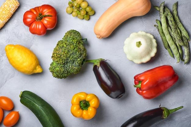 Surtido de frutas frescas y verduras orgánicas de arco iris multicolor sobre fondo de hormigón gris. cocción de alimentos y fondo de alimentos saludables y limpios y maquetas.