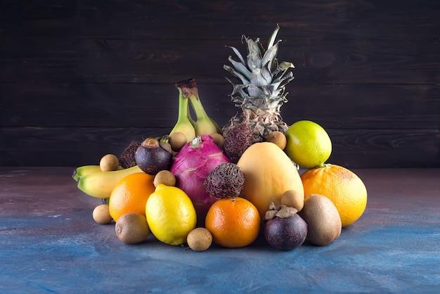 Surtido de frutas tropicales, naranja, piña o piña, lima, mango, fruta del dragón, naranja, banan, rambután y lichi sobre fondo oscuro.