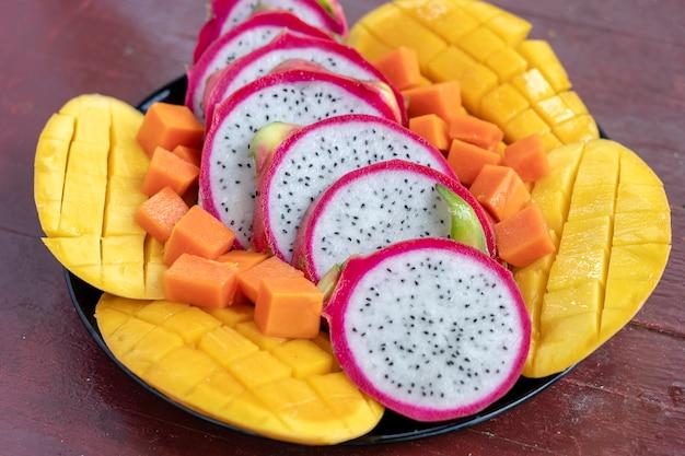 Surtido de frutas tropicales en un plato, de cerca. muchos colores de fondo de frutas tropicales maduras. mango, papaya y pitahaya