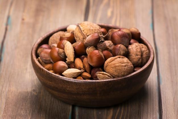 Surtido de frutos secos en cuenco de madera de fondo rústico.