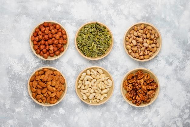 Surtido de frutos secos en platos de cerámica. anacardo, avellanas, nueces, pistacho, nueces, piñones, maní, pasas vista superior.