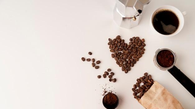 Surtido de granos de café sobre superficie blanca.