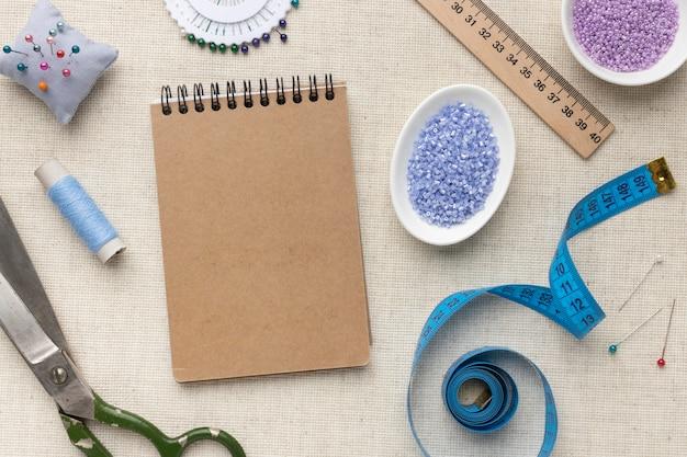 Surtido de herramientas y elementos de confección con bloc de notas vacío