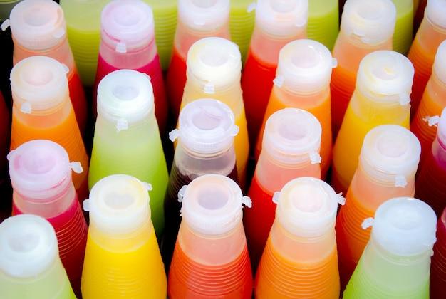 Surtido de jugos fríos de frutas tropicales en botellas.