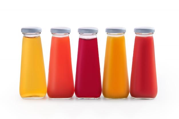 Surtido de jugos en pequeñas botellas de vidrio aisladas en blanco