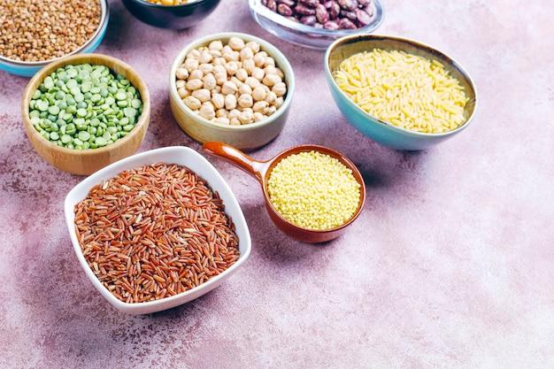 Surtido de legumbres y frijoles en diferentes cuencos sobre fondo de piedra clara. vista superior. alimentos proteicos veganos saludables.