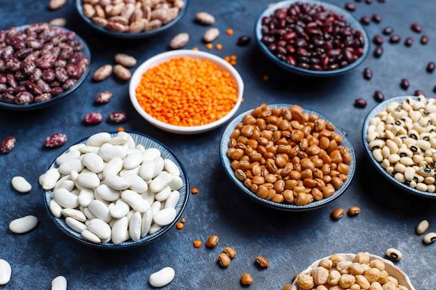 Surtido de legumbres y frijoles en diferentes tazones sobre superficie de piedra clara. vista superior. comida sana de proteínas veganas.
